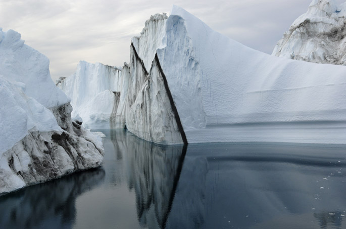Icebergs calved from Jakobshavn Glacier  float to sea near Illulissat. This glacier dumps more ice into the global ocean than any other glacier in the Northern Hemisphere, and is thus Greenland's single biggest contributor to the global sea level rise of one-eight inch per year.Photograph: James Balog/Extreme Ice Survey