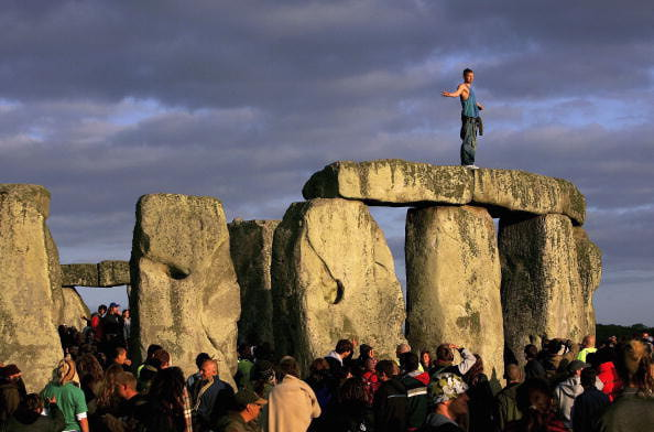 AMESBURY, UNITED KINGDOM - JUNE 21: A man stands on top of Stonehenge as the sun rises over Salisbury Plain on June 21, 2006 in Amesbury, England. Police estimated around 17,000 people travelled to watch the sun rise ove the 5,000 year old stone circle to start the longest day of the year. The all-night party to celebrate the Summer Solstice passed with only four arrests being made. (Photo by Daniel Berehulak/Getty Images)