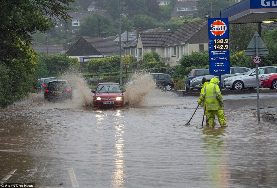 Cars travel through flood water in Helston, south-west Cornwall - Daily Mail August, 2013