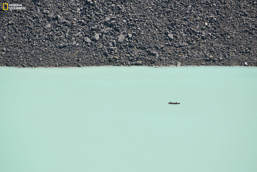 """""""This disorienting photo was taken from a cliff overlooking Lake Louise. Two people are enjoying a canoe ride on the lake's turquoise waters. Even boulders the size of large cars seem like pebbles from a high vantage point."""" Location: Lake Louise, Banff National Park, Alberta, Canada. Photo by Ben Leshchinsky."""