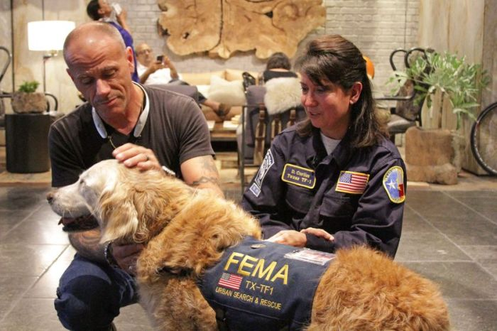 """Bretagne with a firefighter and her owner and handler, Denise Corliss during her """"Dog's Best Day."""" (Photo: BarkPost)"""