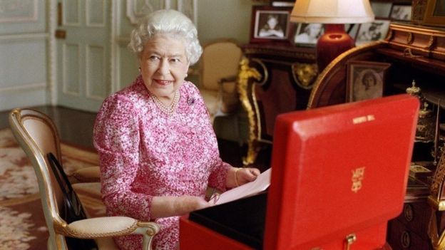 Newly released official photographs show the Queen with her official red box, containing the day's policy papers, cabinet documents, Foreign Office papers and other letters.