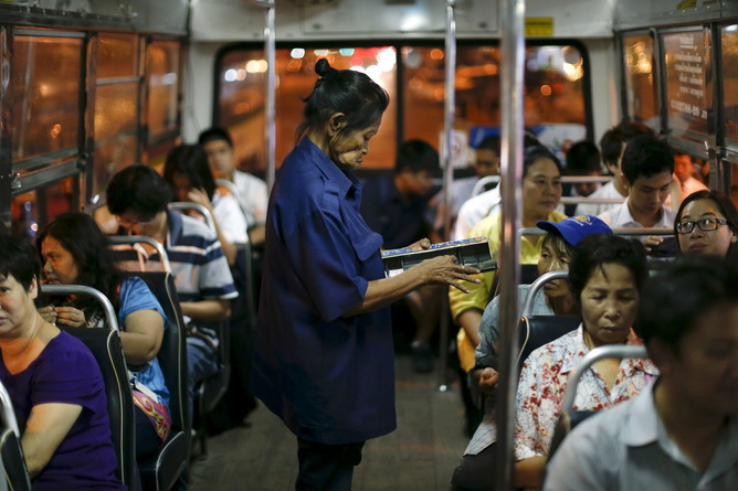Pranom Chartyothin, a 72-year-old bus conductor, sells and collects bus tickets in downtown Bangkok, Thailand, February 3, 2016. Such scenes will only become more common in Thailand as its population rapidly ages, unlike its neighbours with more youthful populations. The World Bank estimates the working-age population will shrink by 11 percent by 2040, the fastest contraction among Southeast Asia's developing countries. Thailand's stage of economic development, the rising cost of living and education, and a population waiting longer to get married are among the reasons it is ageing more quickly than its neighbours. An effective contraception programme in the 1970s also played a part, said Sutayut Osornprasop, a human development specialist at the World Bank in Thailand. Picture taken February 3, 2016. REUTERS/Jorge Silva TPX IMAGES OF THE DAY - RTX269SM
