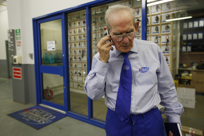 Depot Supervisor Eric Headley, 74, takes a call on his mobile phone while at work for Pimlico Plumbers in London July 29, 2010. Britain announced plans to scrap the fixed retirement age next year, saying it wanted to give people the chance to work beyond 65, but business leaders warned the move would create serious problems. REUTERS/Suzanne Plunkett (BRITAIN - Tags: POLITICS SOCIETY) - RTR2GUL1