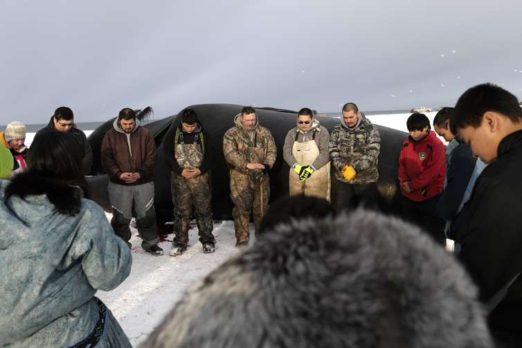 Crawford Patkotak, center, leads a prayer after his crew landed a bowhead whale near Barrow, Alaska. Both revered and hunted by the Inupiat, the bowhead whale serves a symbol of tradition, as well as a staple of food. AP Photo/Gregory Bull
