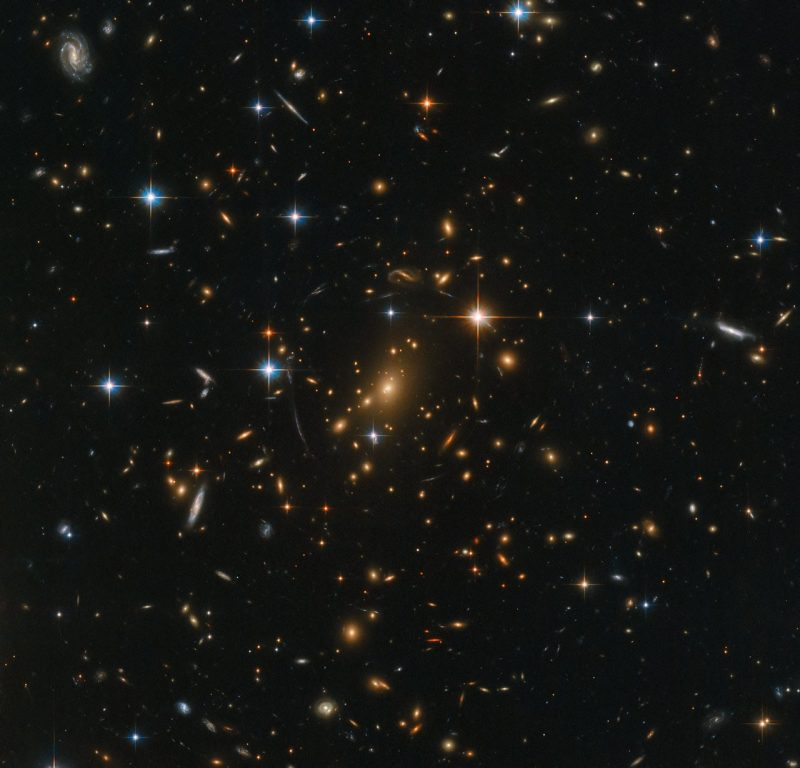 "Here's the original Hubble image of galaxy cluster RXC J0142.9+4438, later ""sonified"" by Russo and Santaguida. NASA wrote: ""Galaxies abound in this spectacular Hubble image; spiral arms swirl in all colors and orientations, and fuzzy ellipticals can be seen speckled across the frame as softly glowing smudges on the sky. Each visible speck of a galaxy is home to countless stars. A few stars closer to home shine brightly in the foreground, while a massive galaxy cluster nestles at the very center of the image; an immense collection of maybe thousands of galaxies, all held together by the relentless force of gravity."" Read more about this image, which is via ESA/ Hubble & NASA, RELICS."